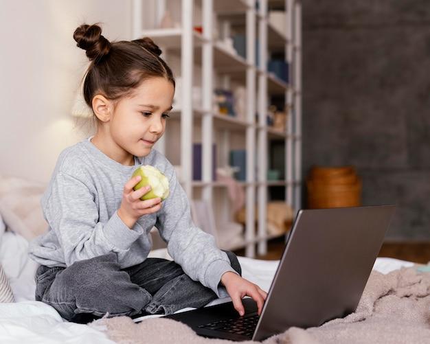 Meisjes in bed kijken naar video op laptop