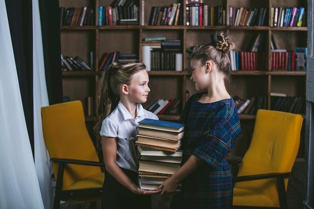 Meisjes in de bibliotheek met boeken op een strikte manier in het onderwijs