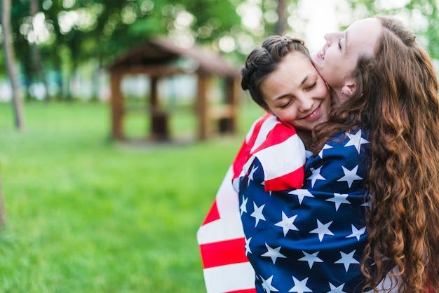 Meisjes in de natuur knuffelen met amerikaanse vlag