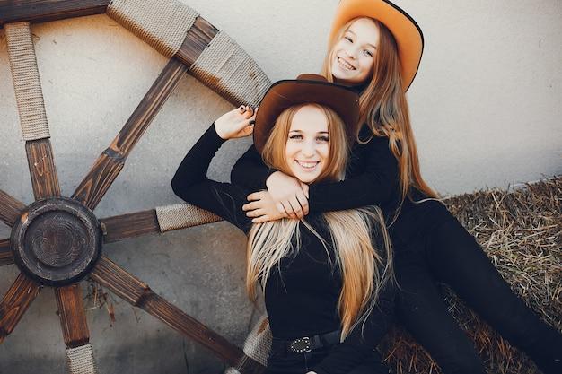 Meisjes in een cowboyshoed op een boerderij