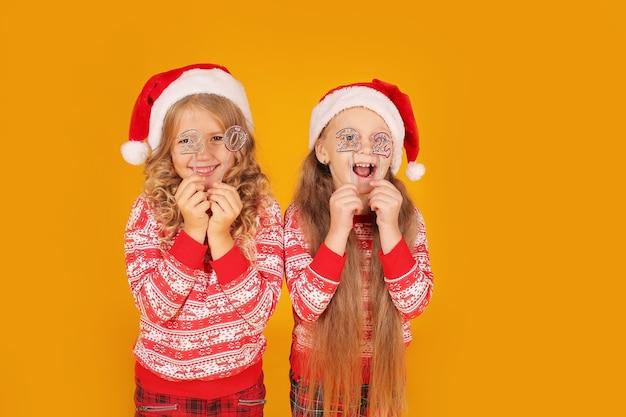 Meisjes in een nieuwjaars jumper broek kerstman hoeden houden de nummers 2022 in hun handen