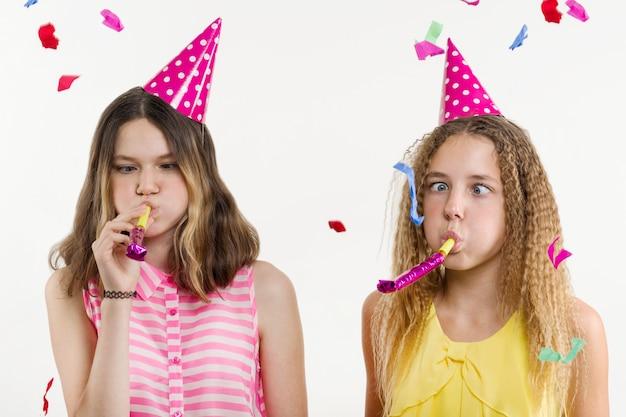 Meisjes in feestelijke hoeden, blazen in de pijpen, kleurrijke confetti