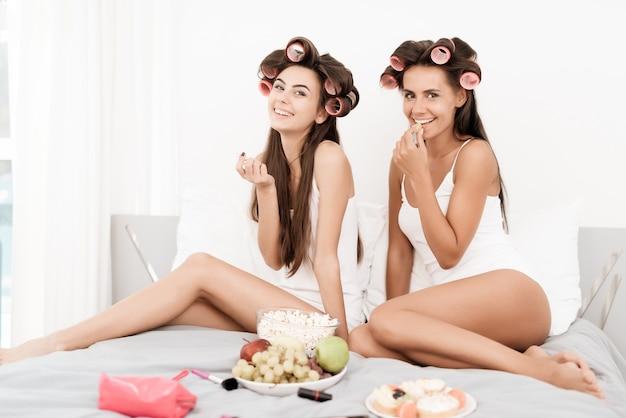 Meisjes in haarkrulspelden zitten op het bed.