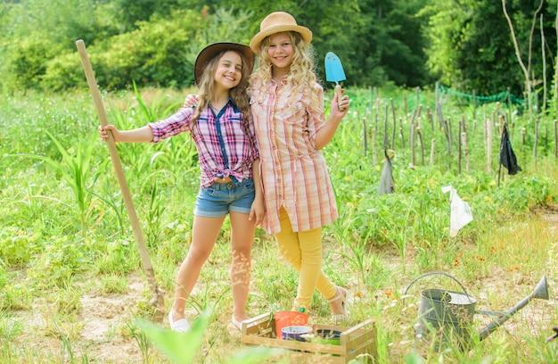 Meisjes in hoeden planten planten. rustieke kinderen natuur achtergrond. eco landbouwconcept. planten en water geven. landbouwconcept. zusters helpen op de boerderij. familie boerderij. kinderen hebben plezier op de boerderij.
