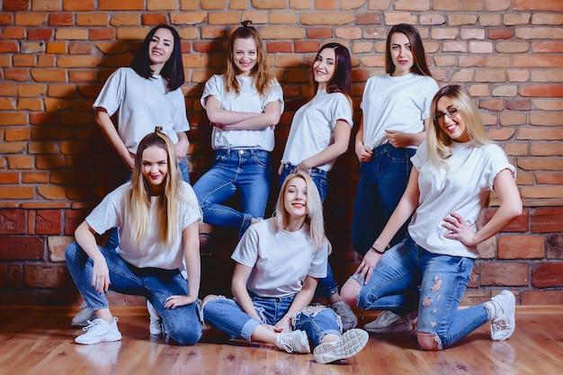 Meisjes in jeans bij achtergrond van bakstenen muur