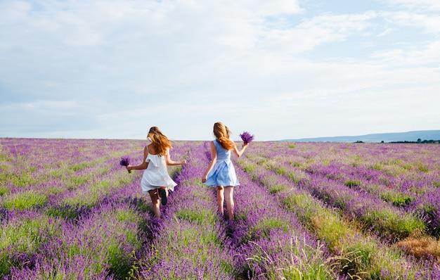Meisjes in jurken die door een lavendelveld lopen