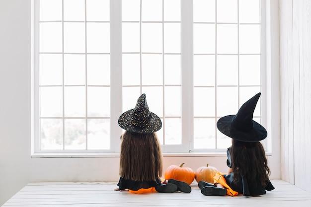 Meisjes in kostuums van halloween die dichtbij venster zitten