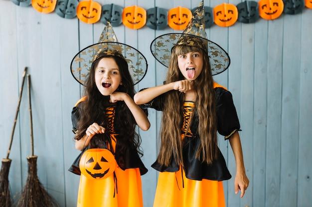Meisjes in kostuums van halloween doen alsof ze zichzelf vermoorden