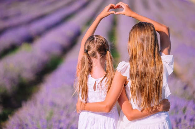 Meisjes in lavendelbloemen veld bij zonsondergang in witte jurken