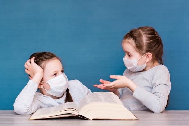 Meisjes in medische maskers in quarantaine lezen en bespreken een boek aan tafel. onderwijs voor geïsoleerde kinderen in een epidemie