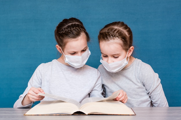 Meisjes in medische maskers in quarantaine lezen zorgvuldig een boek aan tafel. kinderen opvoeden in een epidemie