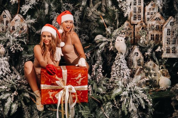 Meisjes in santa claus-hoeden met een groot kerstcadeau in hun handen op een fantastische kerstachtergrond. lachende vrouwen in zwemkleding op de achtergrond van kerstbomen en kleine huizen