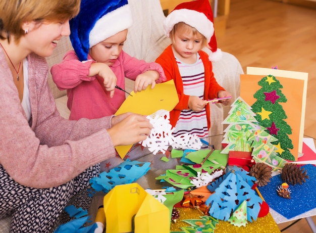 Meisjes in santa hoeden en lachende moeder doet applique werk