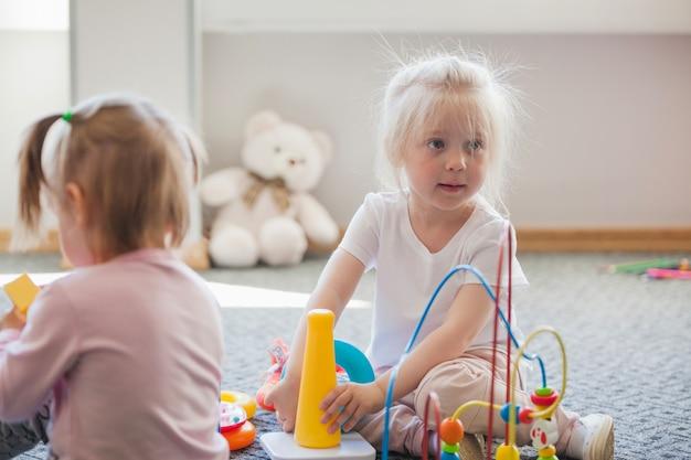 Meisjes in speelkamer met speelgoed
