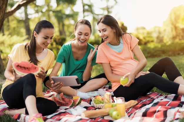 Meisjes in sportkleding. zwangere vrouwen kijken tablet.