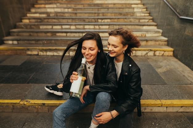 Meisjes in stijlvolle kleding zitten op de trap in de metro