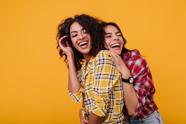 Meisjes in stijlvolle straatkleren lachen oprecht om elkaars grappen. vriendinnen poseren graag voor een gewone foto.