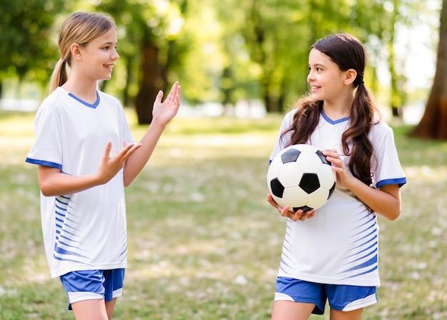 Meisjes in voetbaluitrusting praten