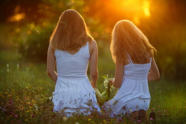 Meisjes in witte katoenen jurken met lang steil haar genieten van het leven, wervelen en dansen op een bloeiend veld van gele bloemen in het warme licht van de zonsondergang
