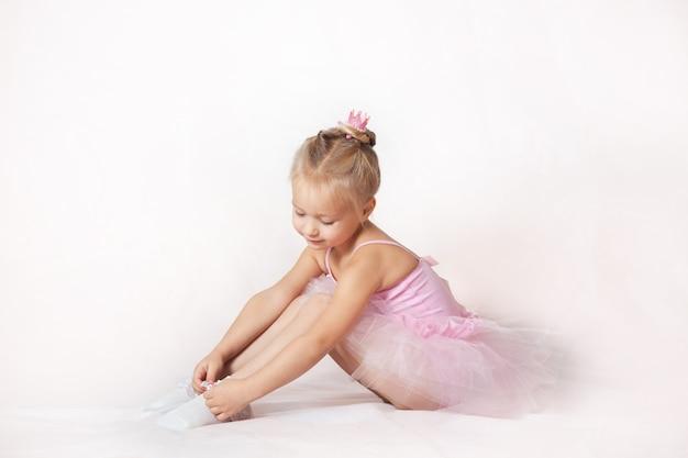 Meisjes jonge ballerina's in roze jurken op een lichte achtergrond