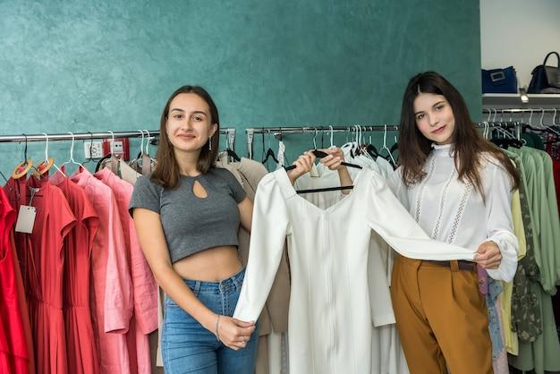 Meisjes kiezen nieuwe kleding in de modewinkel voor een feestje