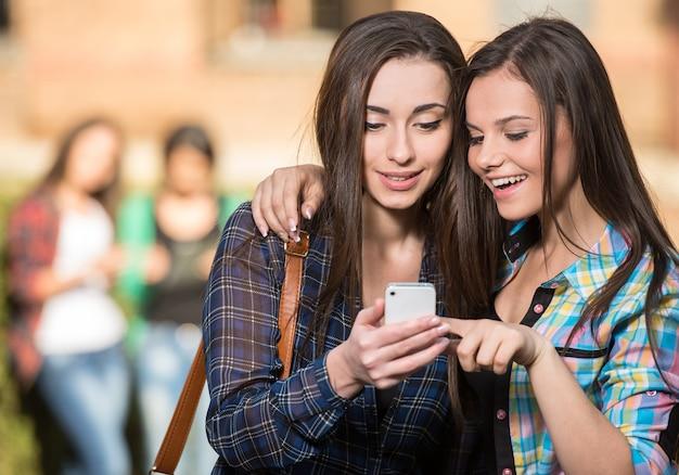 Meisjes knuffel en iets kijkt naar de telefoon.