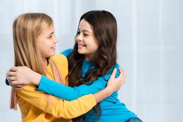 Meisjes knuffelen en kijken naar elkaar