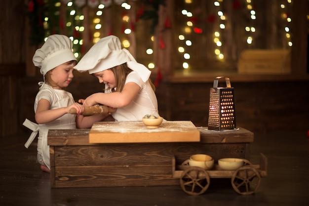 Meisjes koken met een deegroller om deeg uit te rekken, het concept van kindertijd,