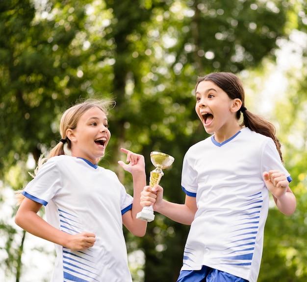 Meisjes krijgen een trofee na het winnen van een voetbalwedstrijd