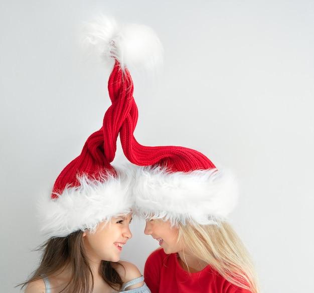 Meisjes lachen elkaar in de kronkelende hoeden van de kerstman