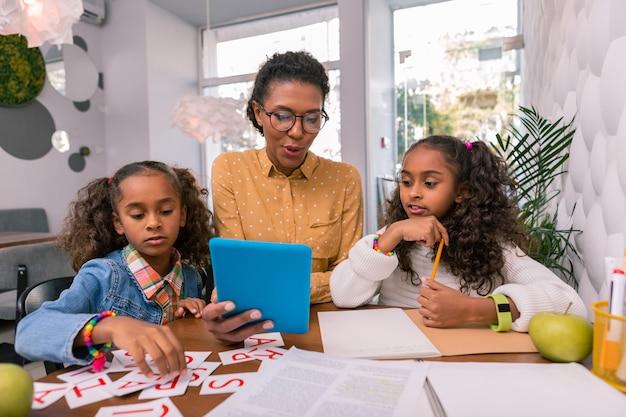 Meisjes lesgeven. vrouw met bril voelt zich geweldig tijdens het lesgeven aan twee kleine meisjes die aan de tafel zitten