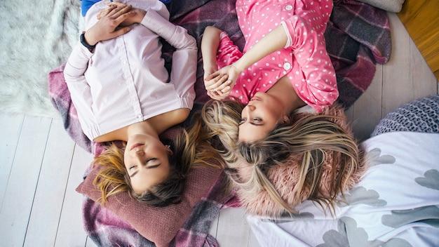 Meisjes logeerpartij. vrijetijdscommunicatie. vrouwelijke beste vrienden die thuis op de vloer rondhangen, chatten.