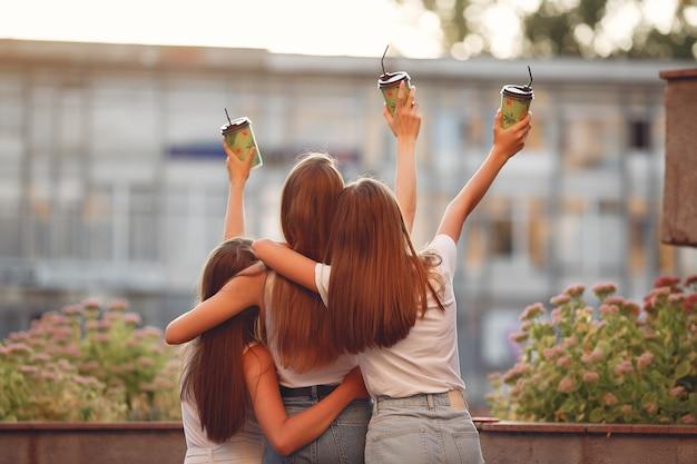 Meisjes lopen in een lentestad en houden koffie in haar hand