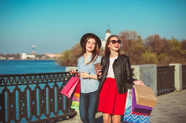 Meisjes lopen met winkelen op stadsstraten