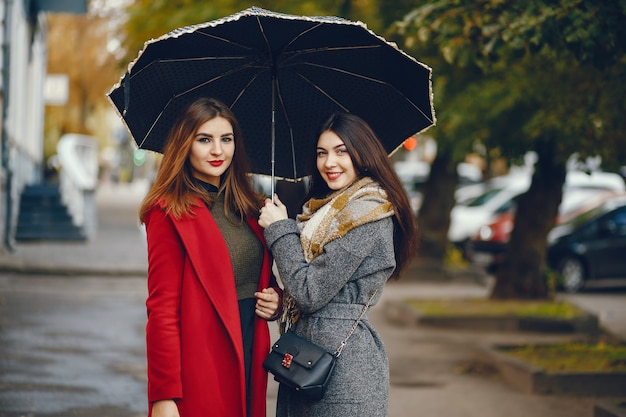 Meisjes lopen. vrouwen met paraplu. dame in een jas.