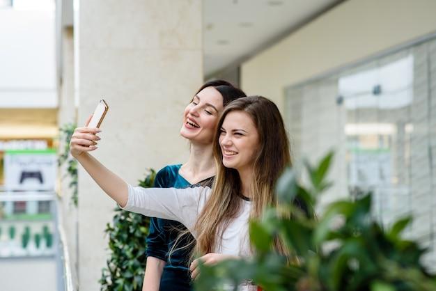 Meisjes maken selfie in het winkelcentrum.