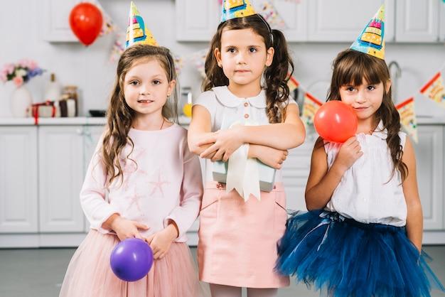 Meisjes met ballonnen en cadeau staan in de keuken