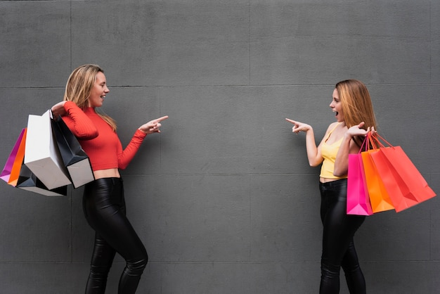 Meisjes met boodschappentassen die naar elkaar wijzen