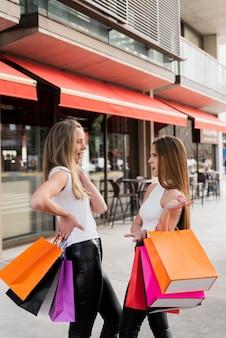 Meisjes met boodschappentassen met een gesprek