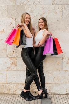 Meisjes met boodschappentassen poseren voor foto