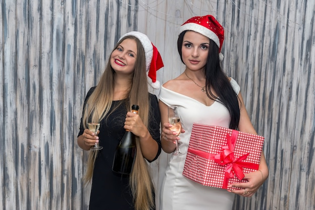 Meisjes met champagne en cadeaudoos in studio