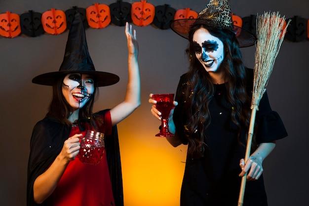 Meisjes met drankjes bij een halloween feest