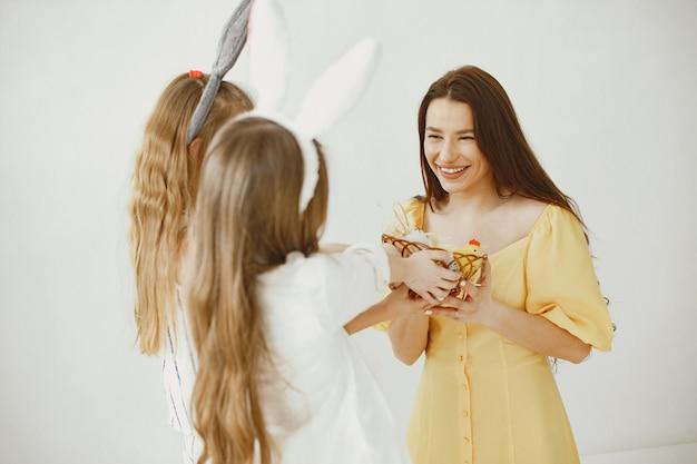 Meisjes met een mandje met eieren. gelukkige moeder in een gele jurk. lang haar bij meisjes.