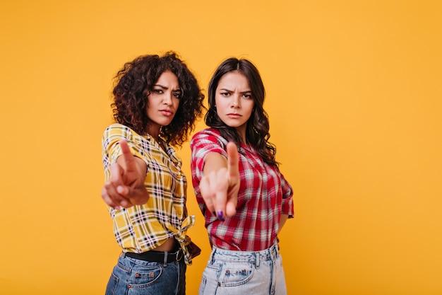 Meisjes met een strenge gezichtsuitdrukking vertonen een stopbord. vriendinnen kijken verwijtend en tonen wijsvingers
