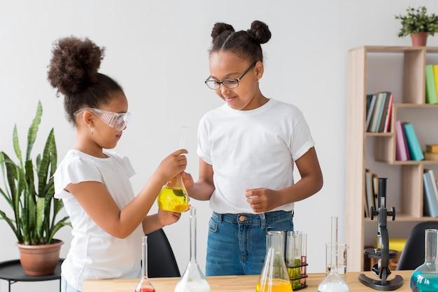 Meisjes met een veiligheidsbril die scheikundige experimenten doen
