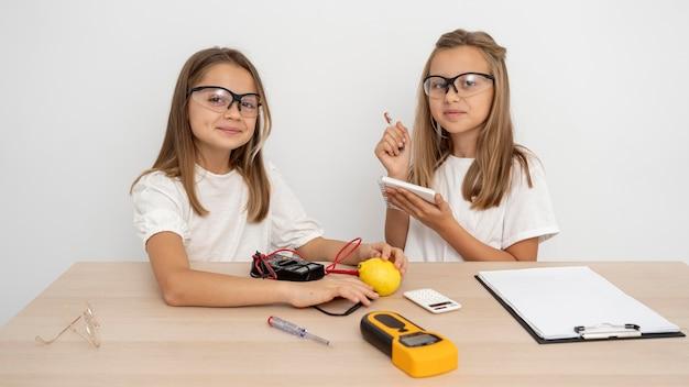 Meisjes met een veiligheidsbril die wetenschappelijke experimenten doen