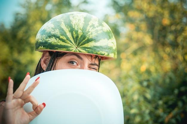 Meisjes met een watermeloenhoed die een wit bord vasthoudt en haar gezicht verbergt