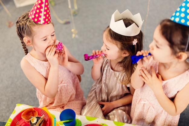 Meisjes met feestspeelgoed op verjaardag
