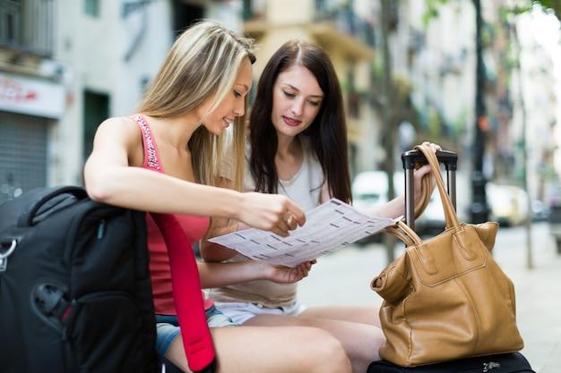 Meisjes met kaart voor het lezen van de bagage