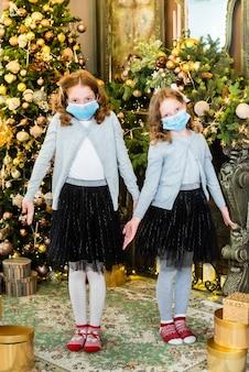 Meisjes met medische maskers bij de kerstboom zijn verrast en verdrietig